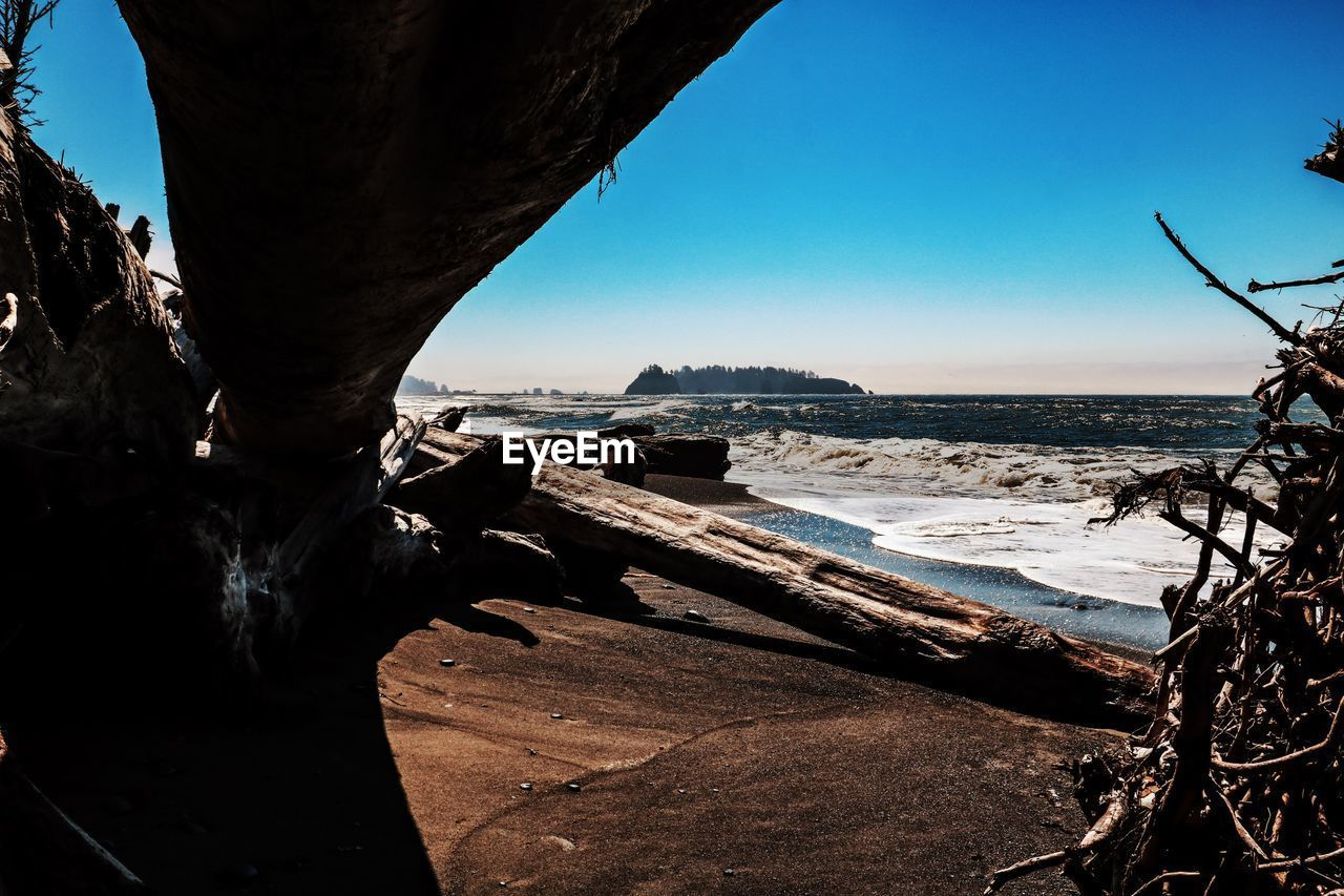 water, sea, sky, nature, day, land, no people, beach, beauty in nature, clear sky, wave, scenics - nature, rock, motion, sport, outdoors, architecture, sunlight, rock - object, driftwood