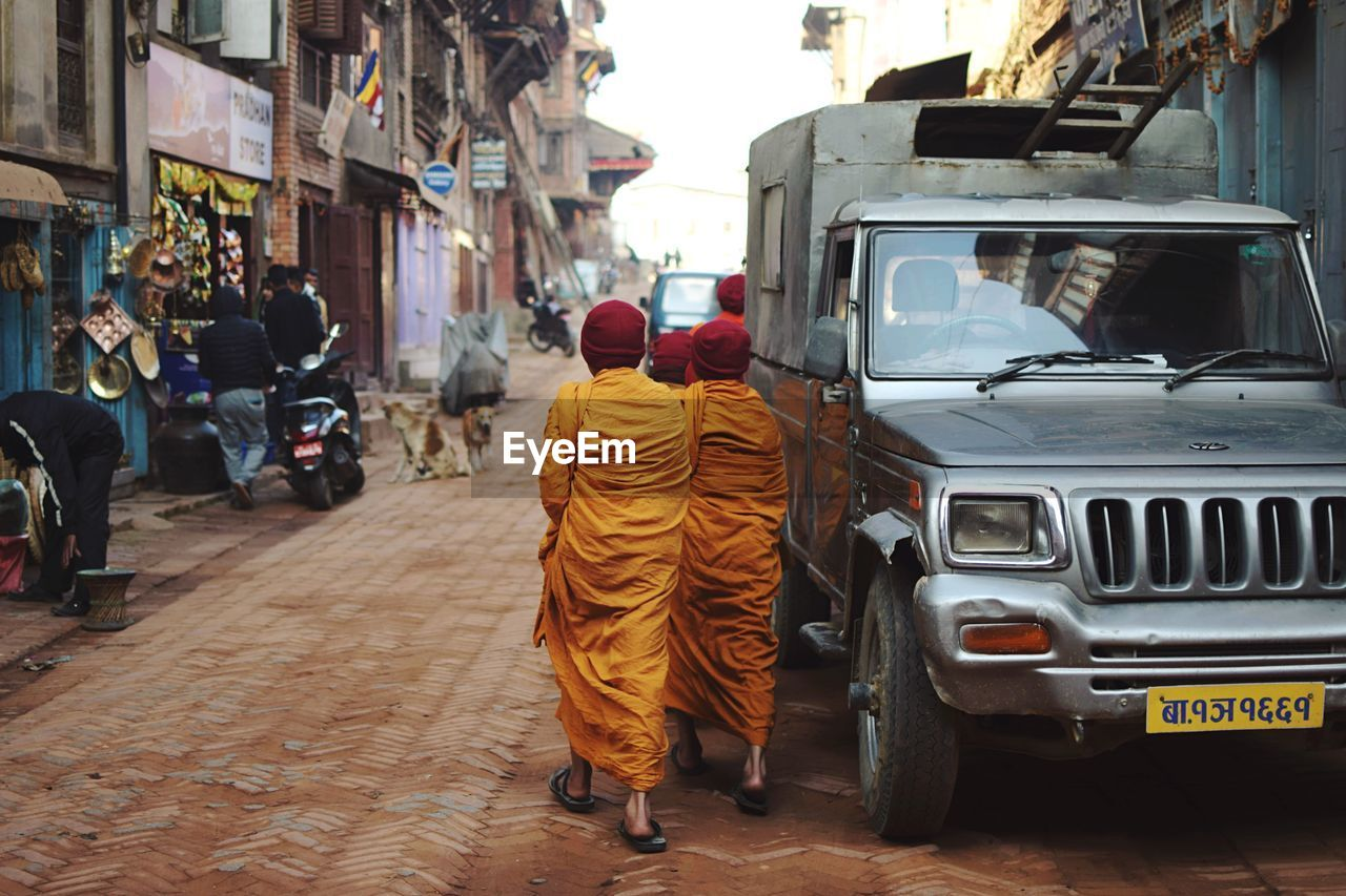 REAR VIEW OF PEOPLE ON ROAD