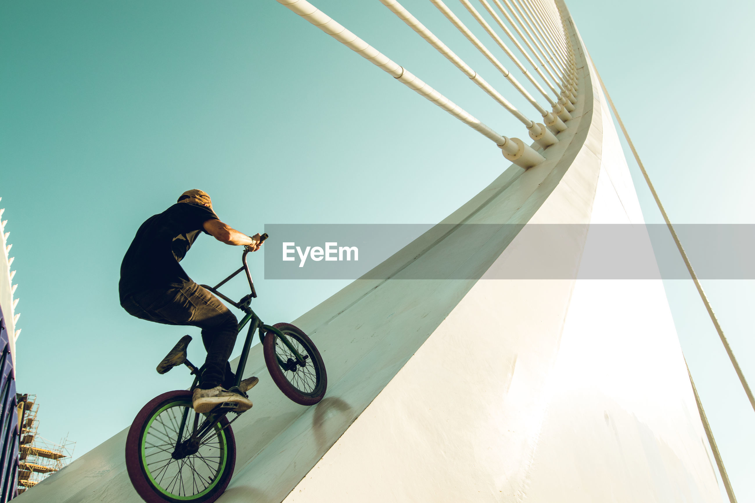 Low angle view of man riding bicycle on built structure against sky