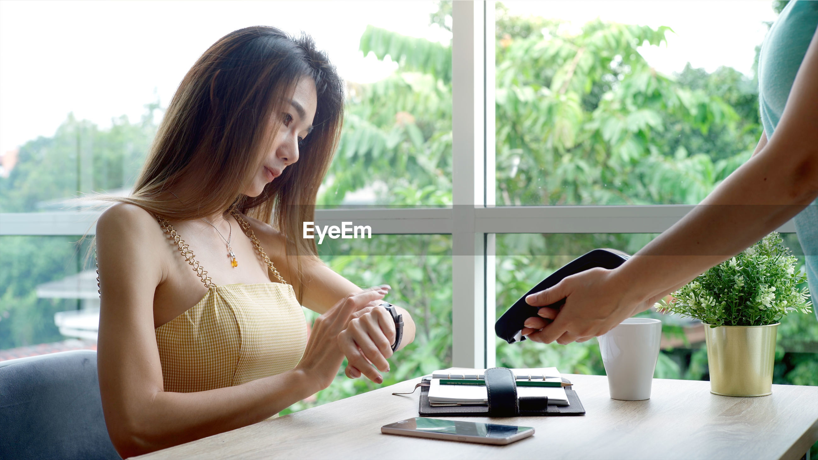 Young woman paying through smart watch to waitress in cafe