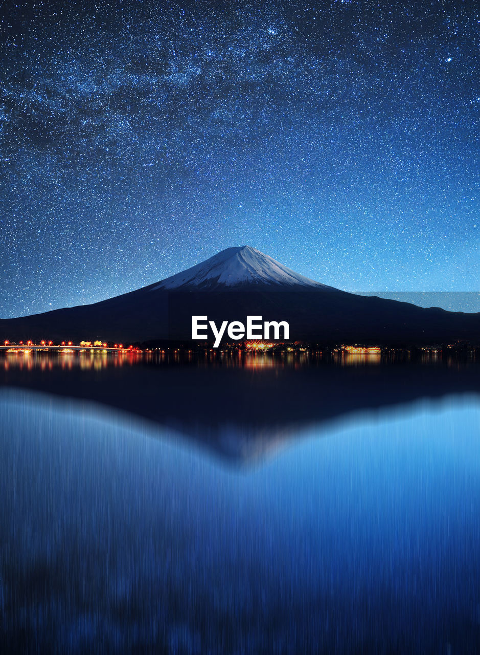 Distant View Of Volcanic Mountain With Reflection On Lake Against Star Field At Night