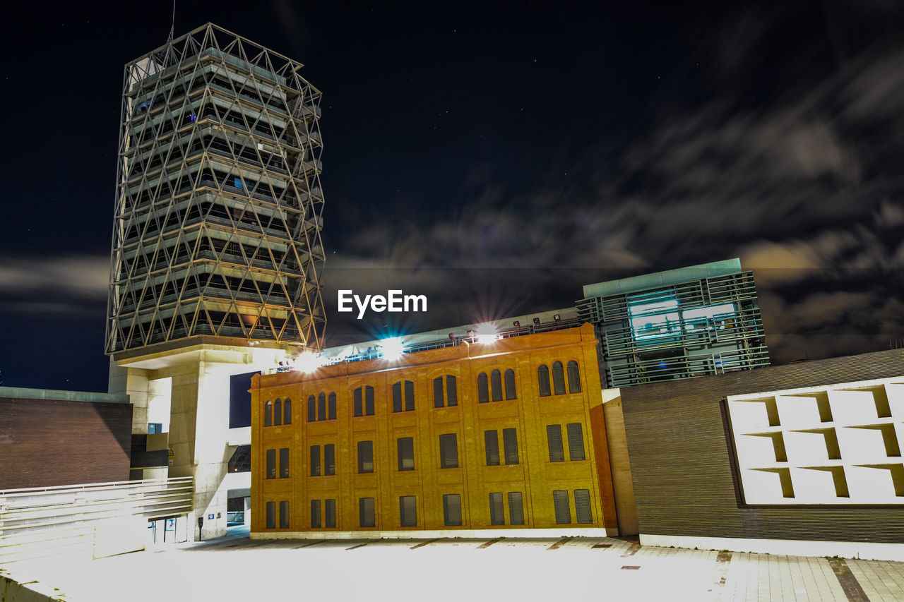 LOW ANGLE VIEW OF ILLUMINATED BUILDING AGAINST SKY DURING WINTER