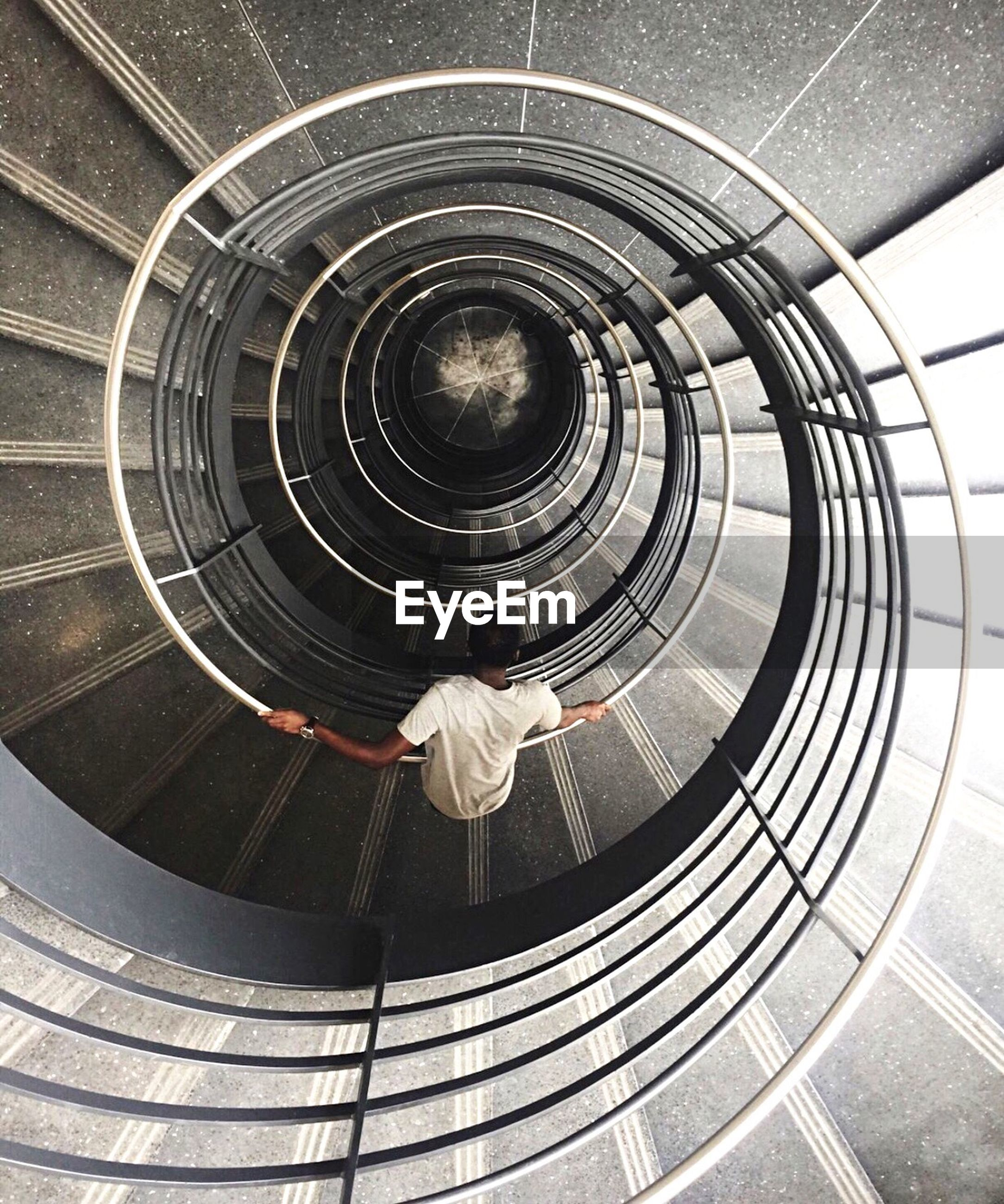 Directly above shot of man on spiral staircase