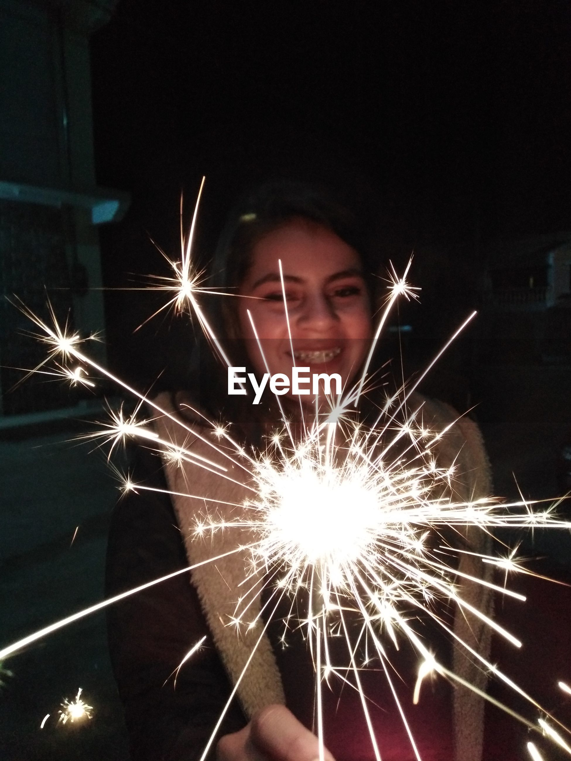Cheerful teenage girl holding sparkler at night