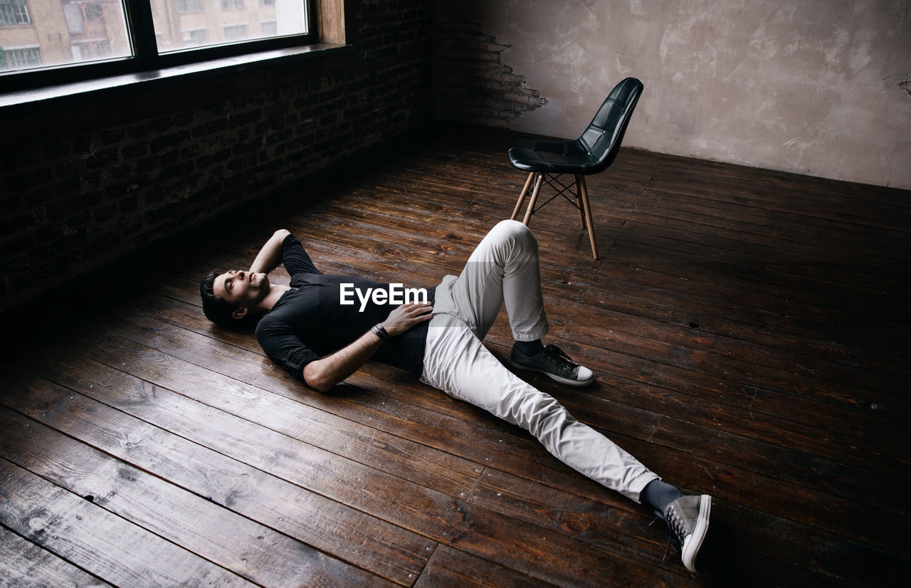 High Angle View Of Young Man Lying On Hardwood Floor