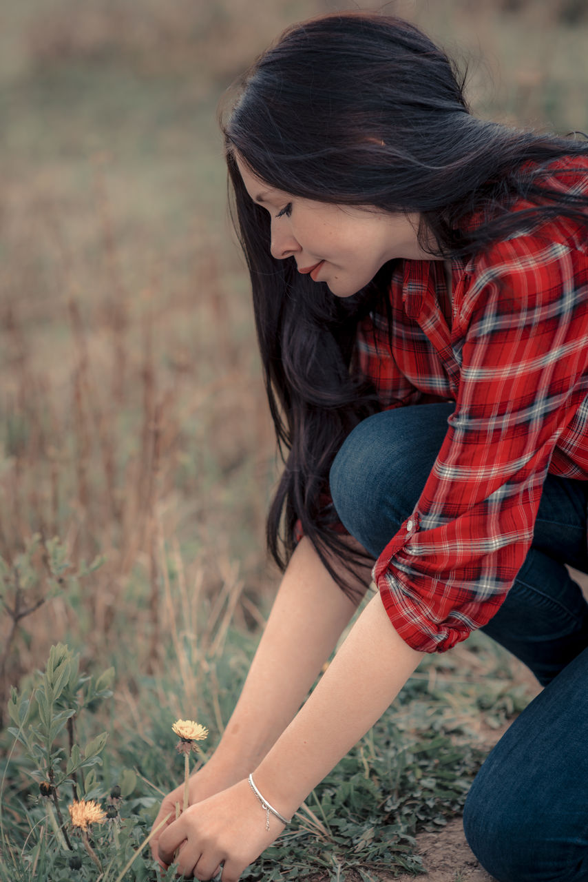 Young Woman Picking Up Yellow Flower On Field
