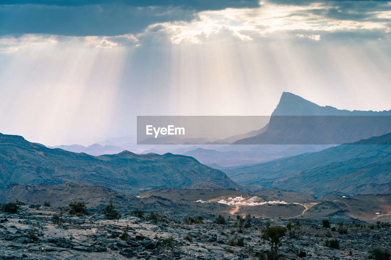 Rays of sunlight shine through scattered clouds on small village in jebel shams , oman.