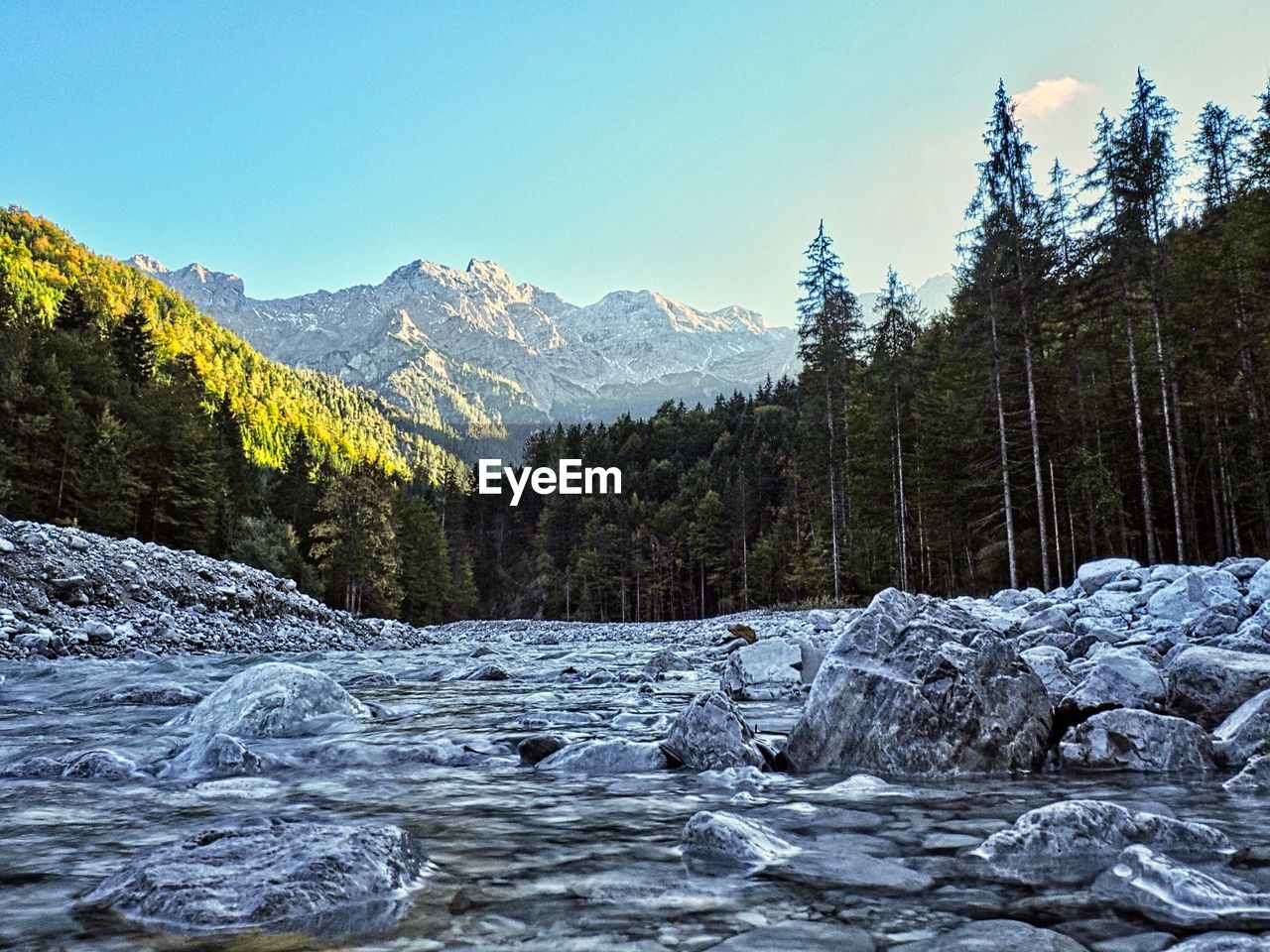 mountain, beauty in nature, sky, scenics - nature, tree, water, plant, nature, tranquility, non-urban scene, tranquil scene, mountain range, cold temperature, no people, day, winter, rock, waterfront, clear sky, flowing water, outdoors, flowing, snowcapped mountain