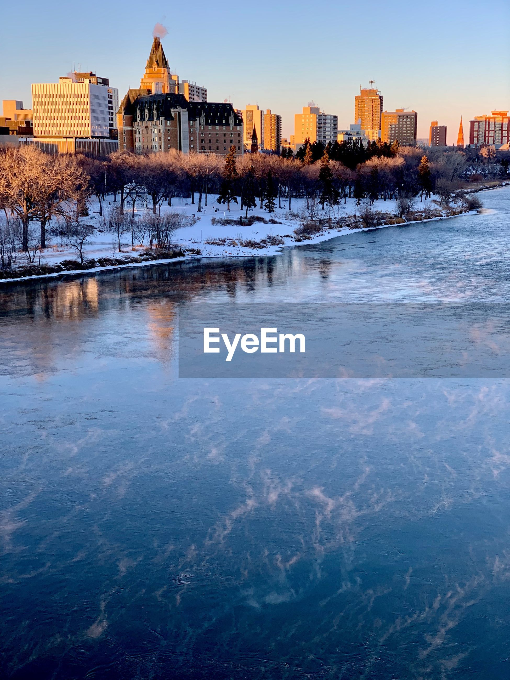 Frozen river by buildings against clear sky during sunset