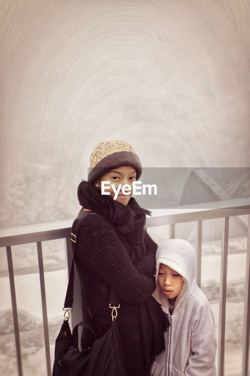Portrait of smiling woman with son by railing during winter