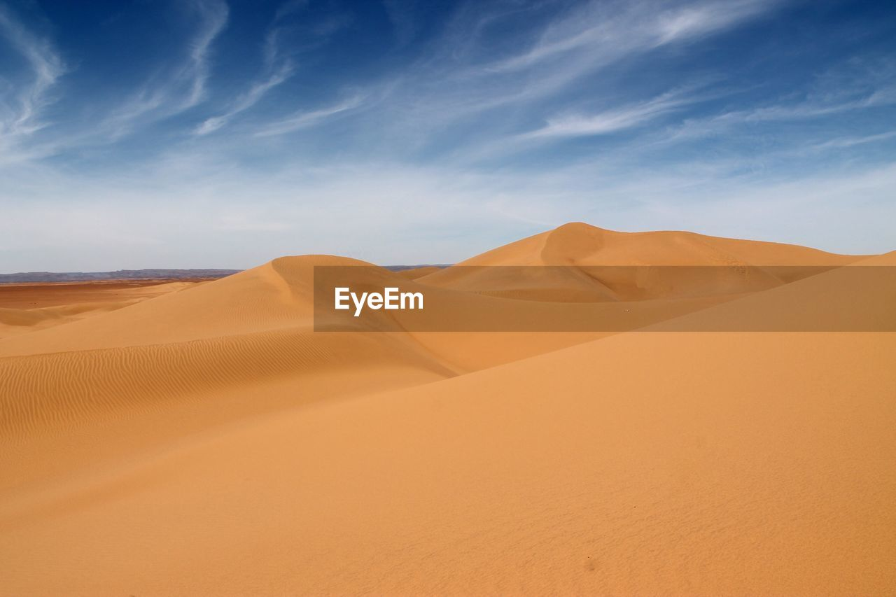Sand Dune In Desert Against Cloudy Sky During Sunny Day