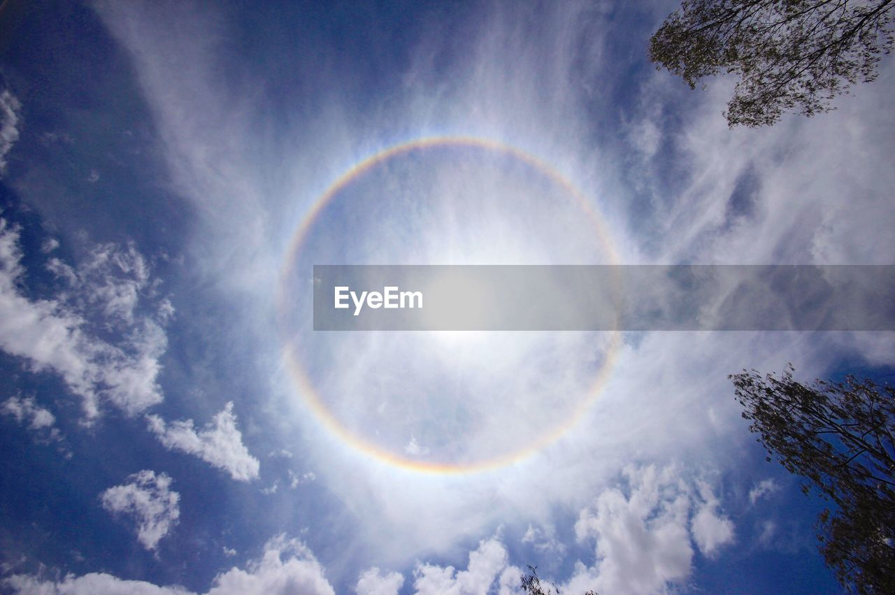 sky, cloud - sky, beauty in nature, low angle view, scenics - nature, nature, no people, tranquil scene, tranquility, rainbow, idyllic, sunlight, day, outdoors, sun, circle, geometric shape, tree, halo, lens flare, brightly lit