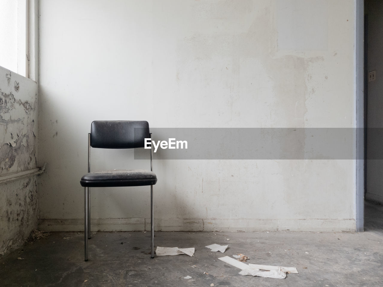 EMPTY CHAIR AGAINST WALL IN ABANDONED ROOM