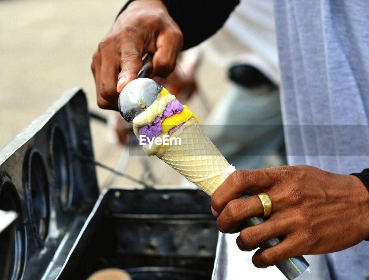 Close-Up Of Vendor Scooping Ice Cream To Put In Cone