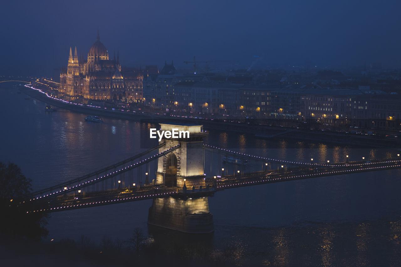 Illuminated Chain Bridge Over River At Night