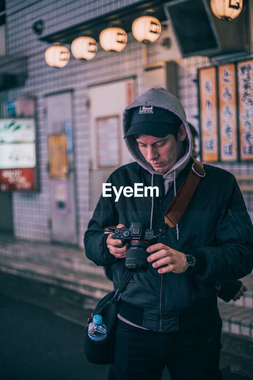 one person, young adult, holding, photography themes, front view, technology, standing, three quarter length, camera - photographic equipment, lifestyles, real people, young men, focus on foreground, clothing, leisure activity, men, communication, photographing, warm clothing, outdoors, photographer