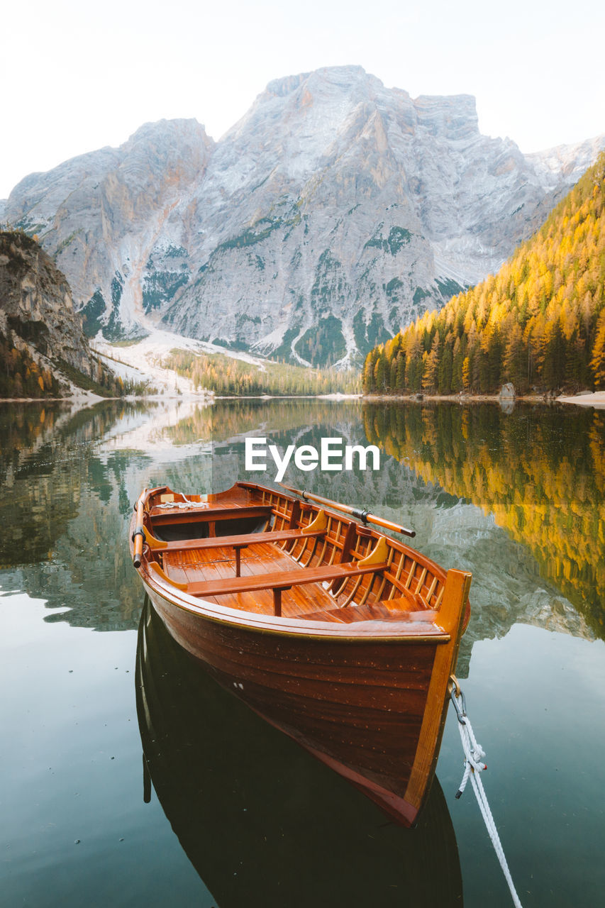 Boat moored on lake by mountain