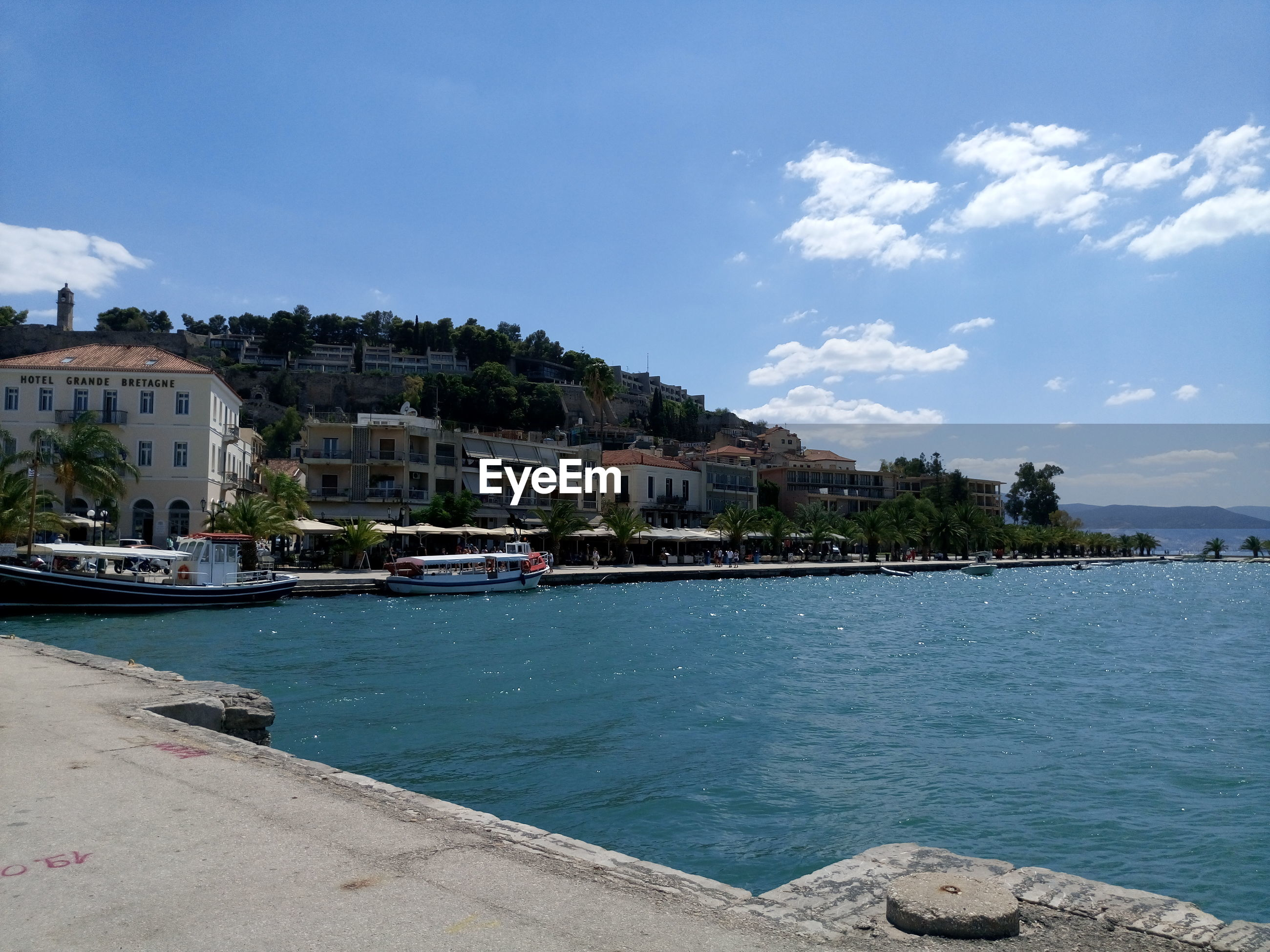 SCENIC VIEW OF SEA BY TOWN AGAINST SKY