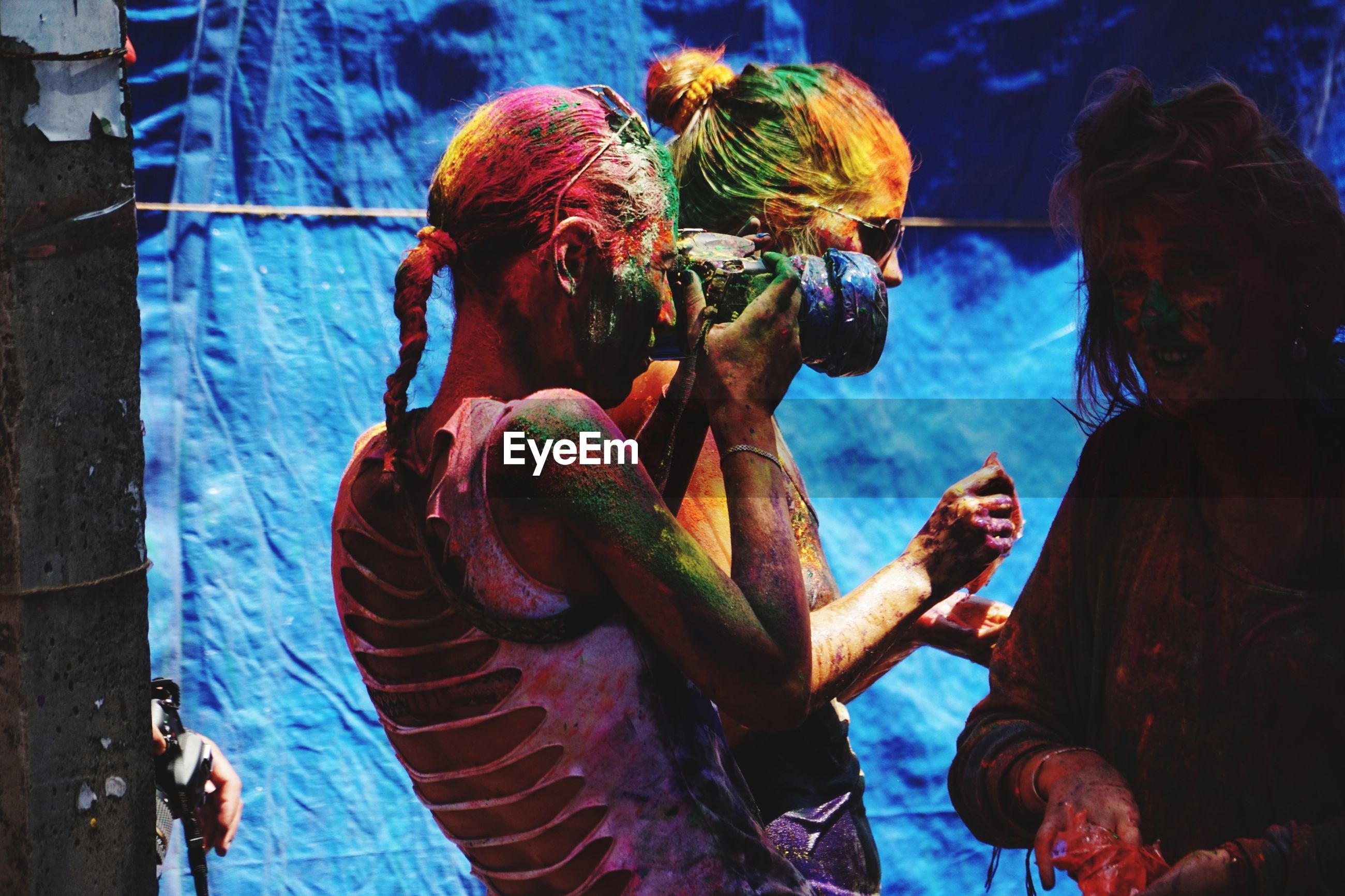 Woman photographing friends playing holi