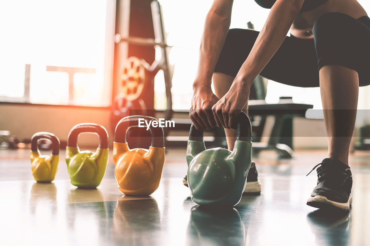 lifestyles, indoors, real people, sports training, sport, sitting, wellbeing, leisure activity, people, healthy lifestyle, sports clothing, focus on foreground, exercising, weight, women, gym, weights, adult, human body part, weight training