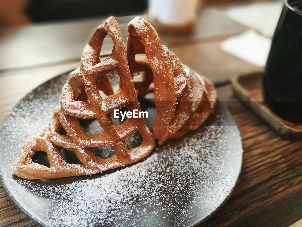 Close-Up Of Waffle With Powdered Sugar On Table