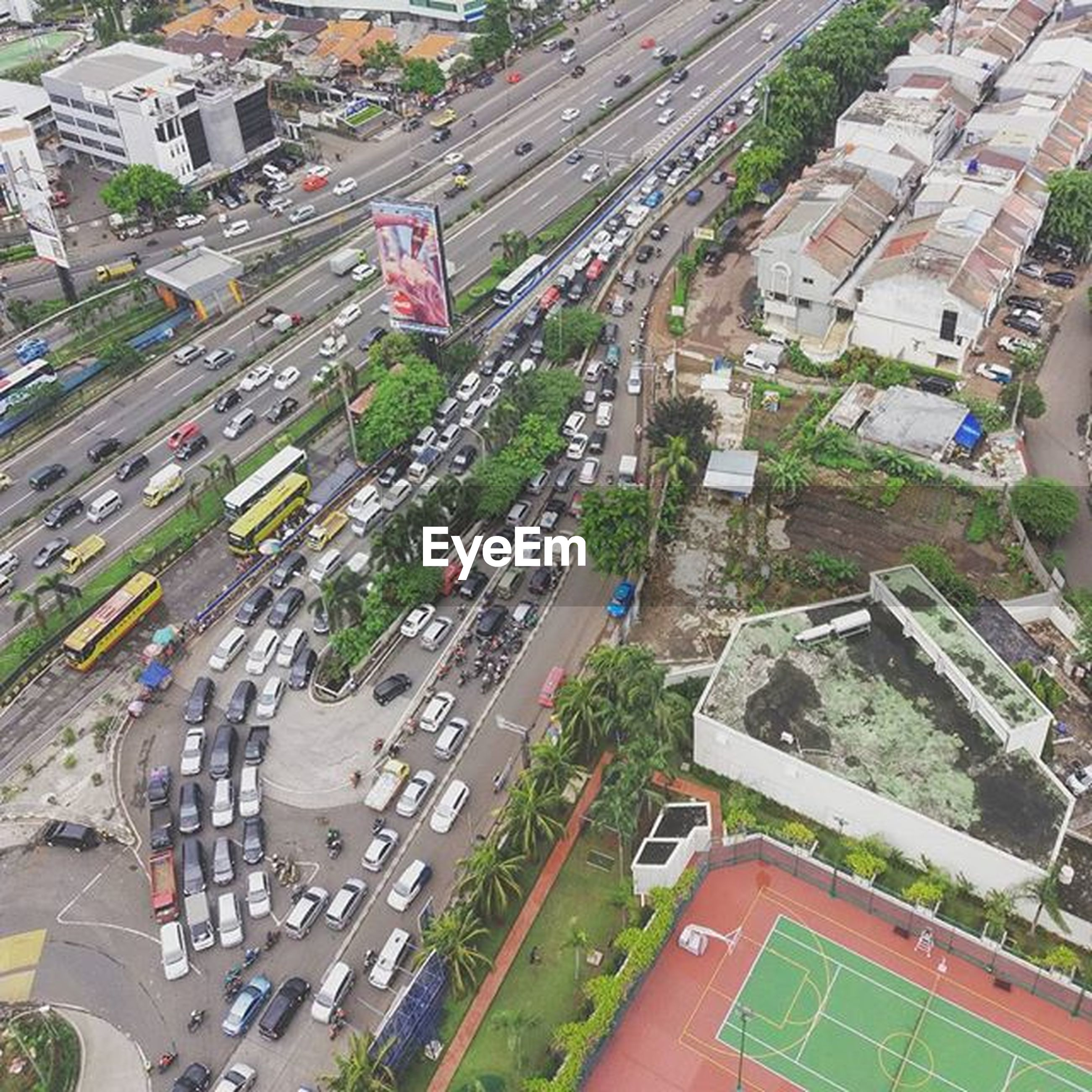 transportation, high angle view, car, road, building exterior, land vehicle, city, architecture, street, built structure, mode of transport, traffic, road marking, city life, city street, aerial view, cityscape, vehicle, elevated view, highway