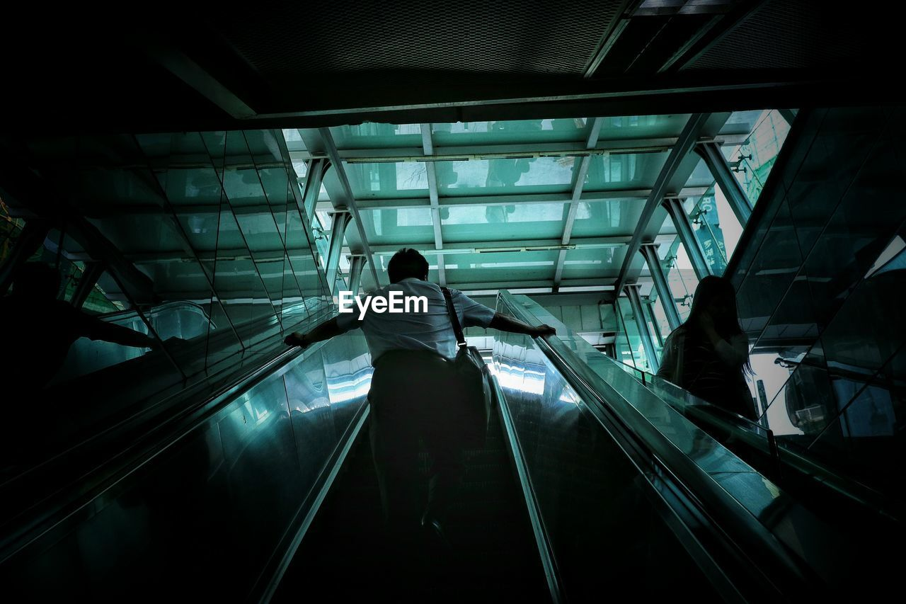 Low Angle View Of Man On Escalator