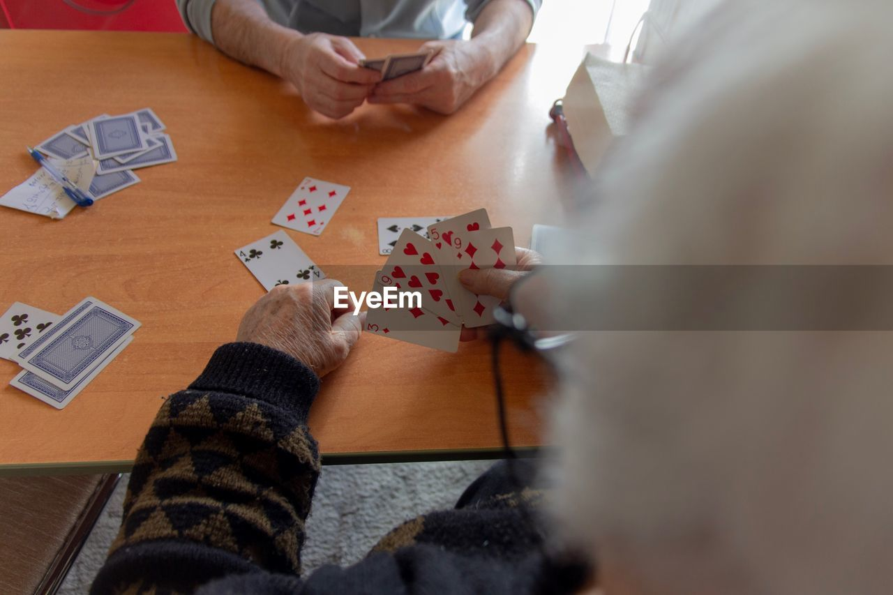 High angle view of people playing poker on table at home