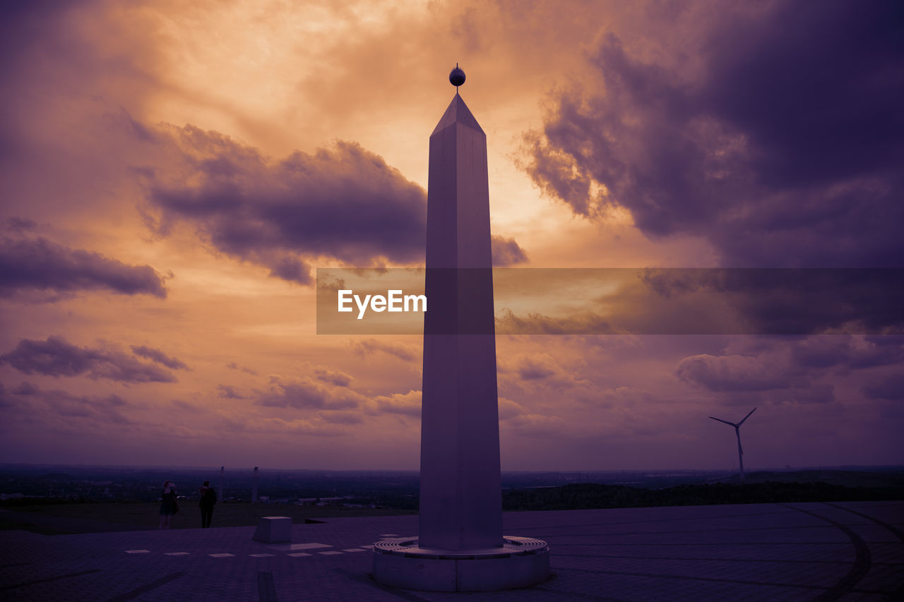 sky, cloud - sky, sunset, architecture, built structure, nature, building exterior, orange color, tower, no people, religion, belief, memorial, building, silhouette, outdoors, beauty in nature, tall - high, the past, purple