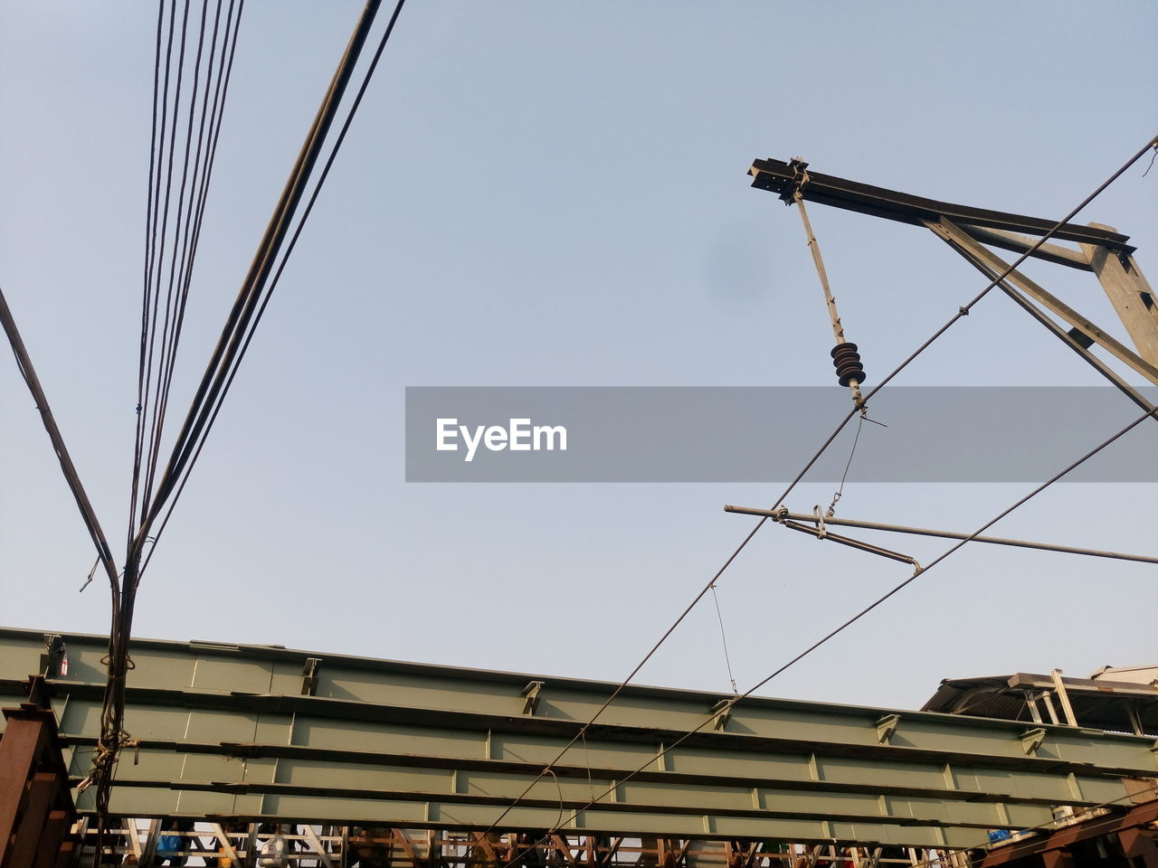 Low Angle View Of Cables Over Railroad Station Against Clear Sky