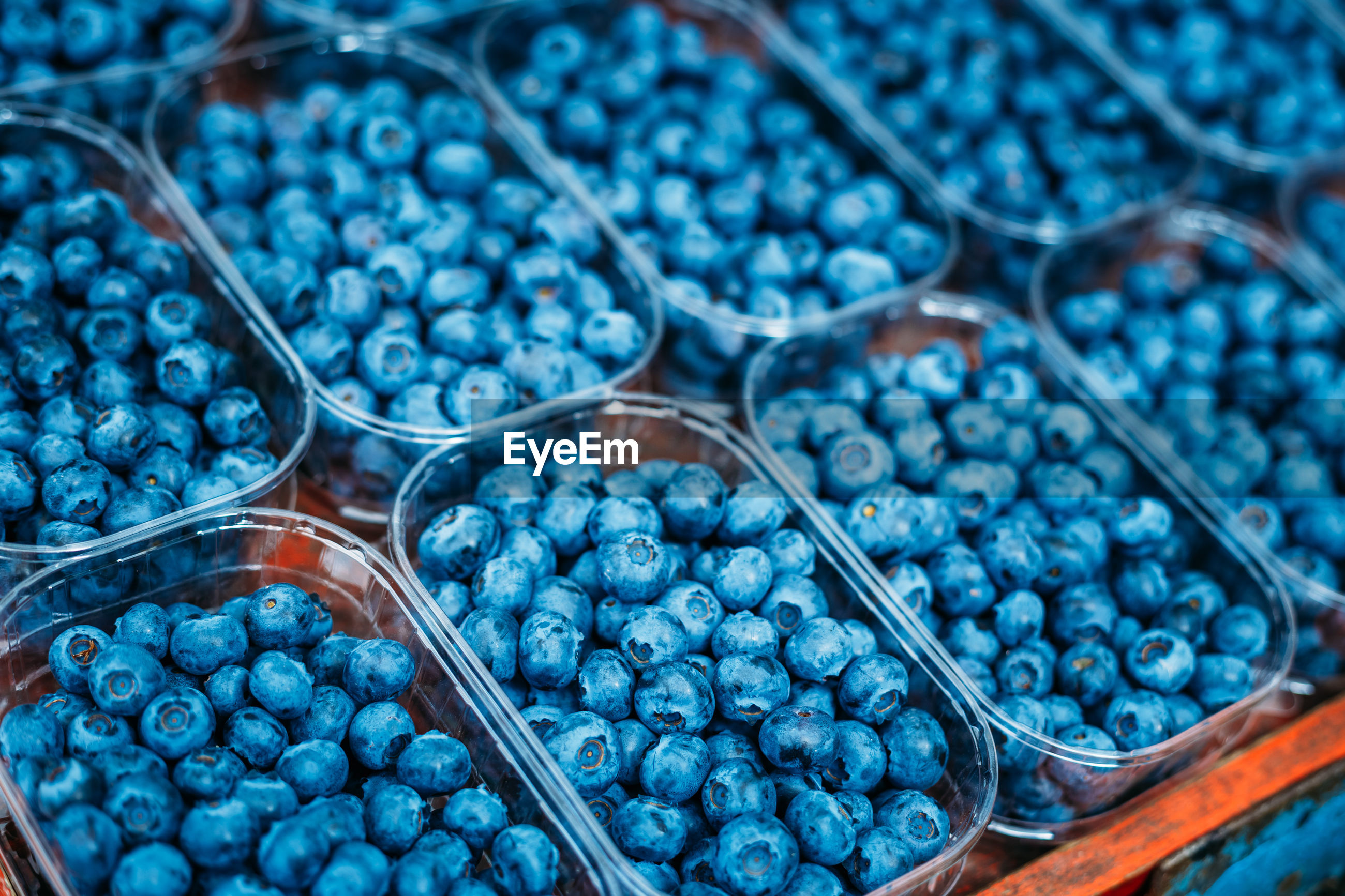 Close-up of blueberries in containers for sale at market