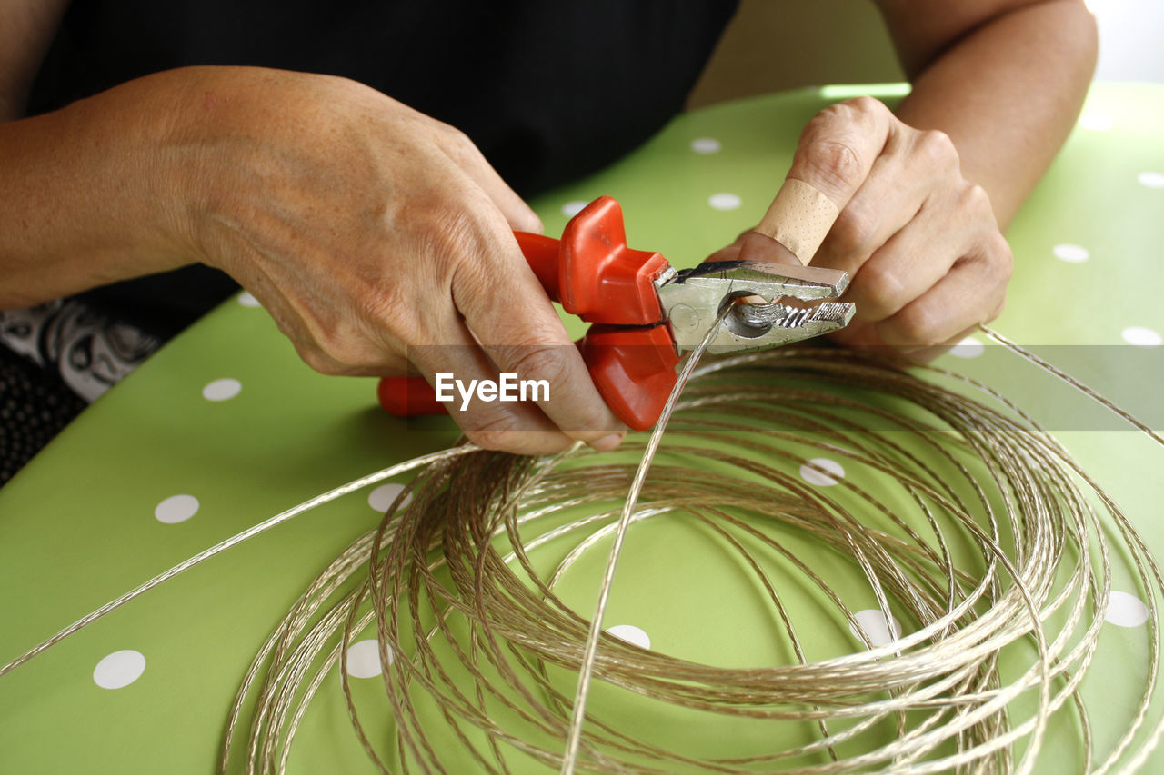 Midsection Of Woman Cutting Cable On Table