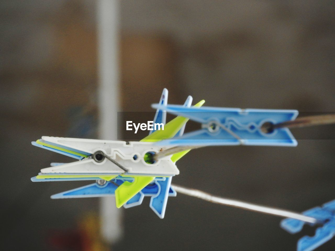 clothespin, focus on foreground, no people, clothesline, blue, close-up, hanging, airplane, air vehicle, toy, animal representation, animal, representation, day, nature, creativity, selective focus, laundry, outdoors, group of objects, plane