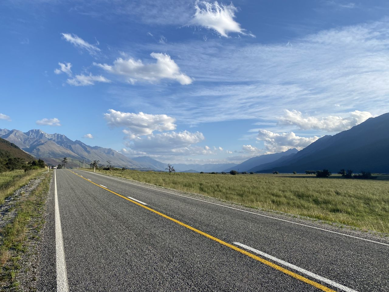 mountain, sky, road, transportation, cloud - sky, road marking, direction, marking, scenics - nature, sign, beauty in nature, the way forward, nature, no people, day, environment, landscape, mountain range, symbol, tranquil scene, diminishing perspective, outdoors, dividing line