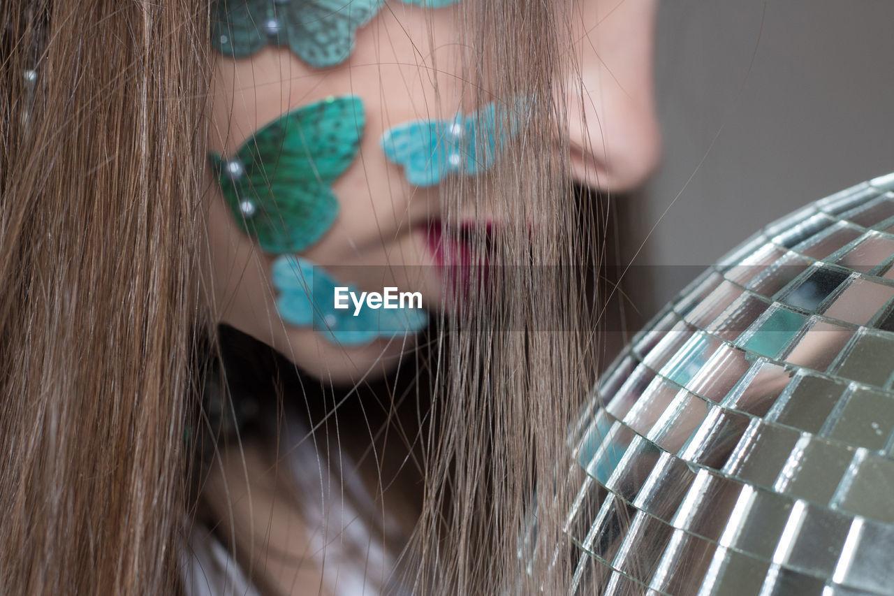 Close-up of woman wearing artificial butterflies on cheek by disco ball