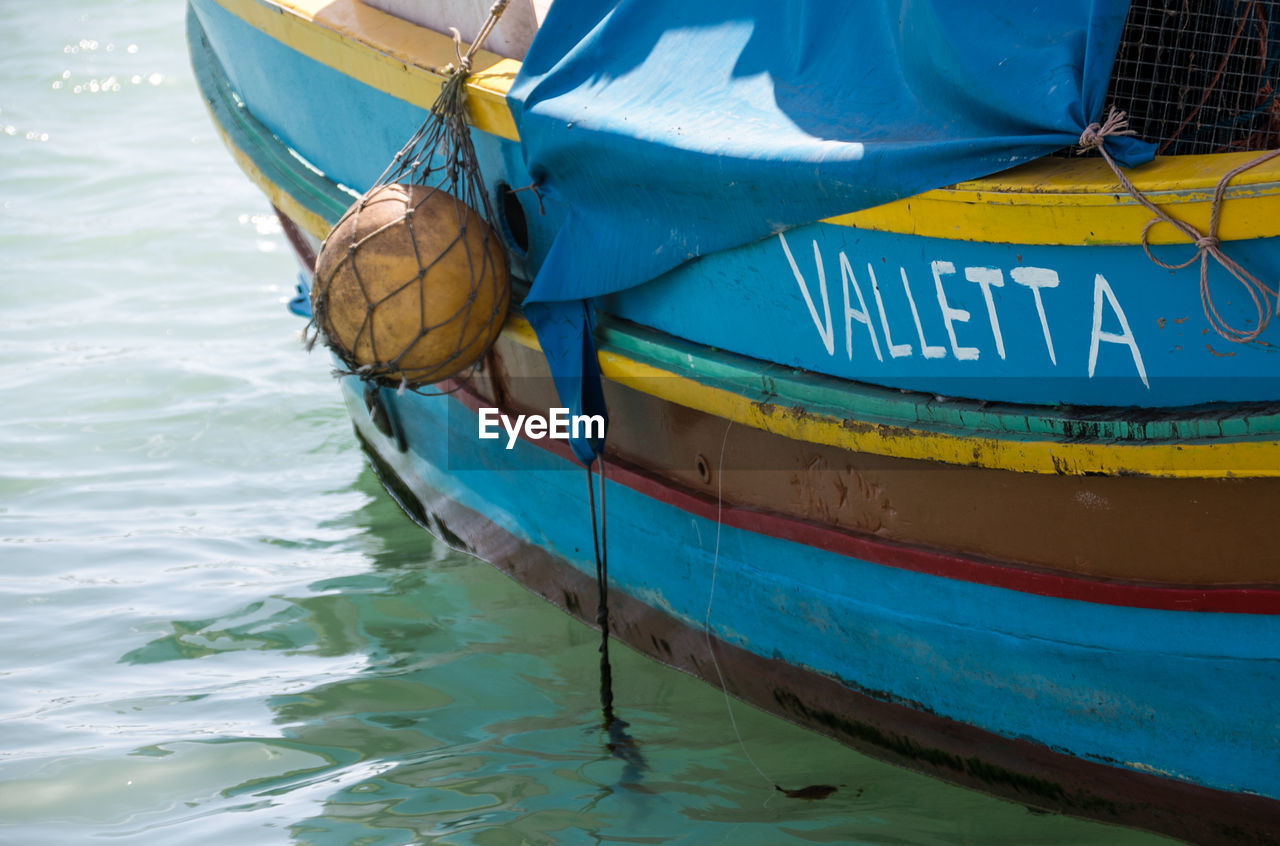 water, nautical vessel, transportation, day, no people, mode of transportation, nature, moored, blue, outdoors, yellow, close-up, text, sea, western script, waterfront, protection, rope, inflatable