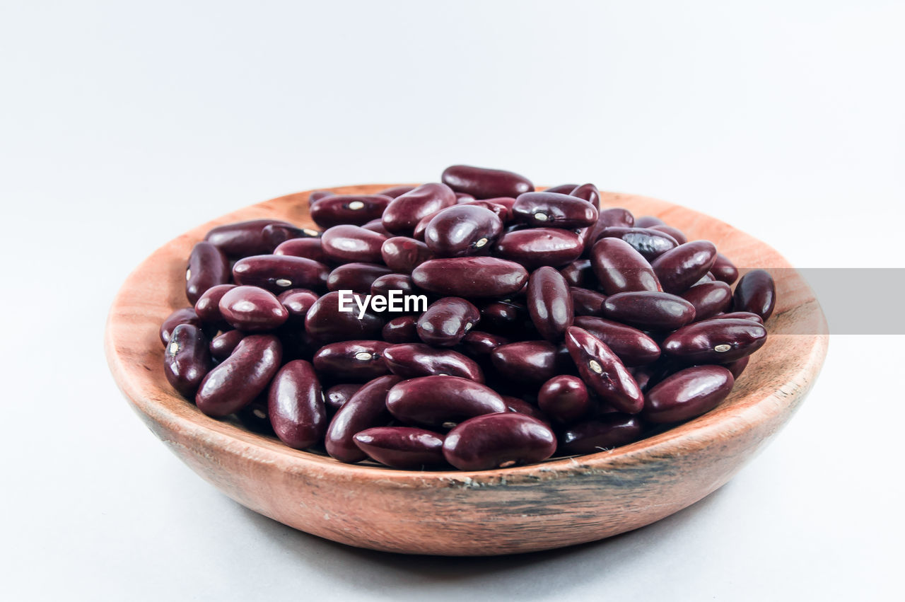 Close-up of beans in wooden container against white background