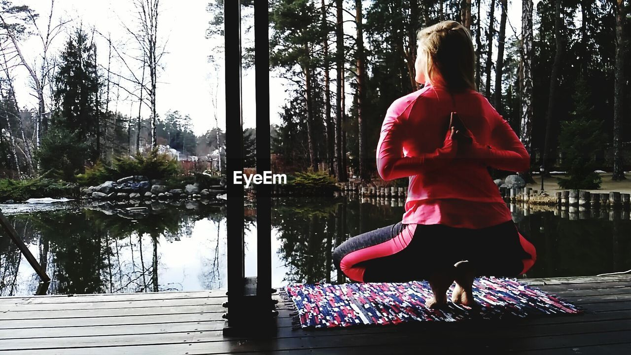 Rear view full length of woman doing yoga by pond on boardwalk