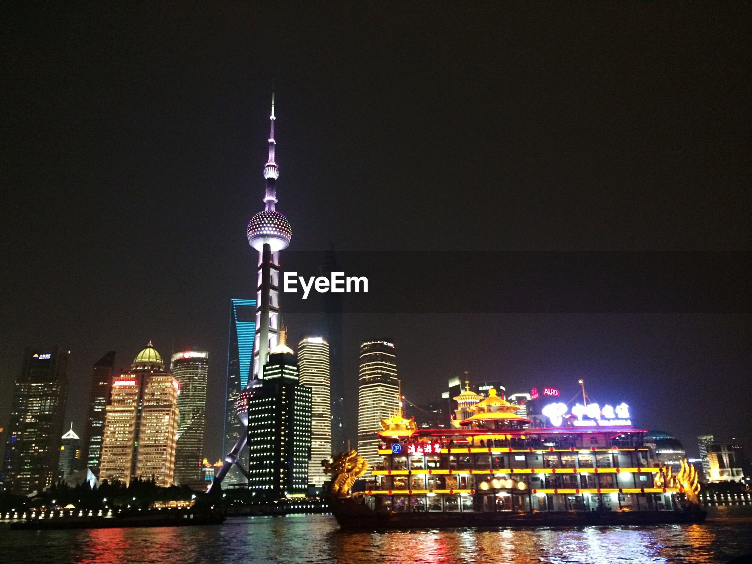 architecture, building exterior, built structure, illuminated, city, night, tower, tall - high, skyscraper, waterfront, water, cityscape, modern, travel destinations, river, capital cities, office building, urban skyline, famous place, international landmark