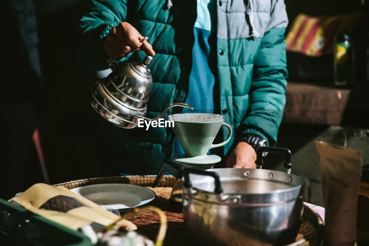 Midsection of man preparing coffee in kitchen