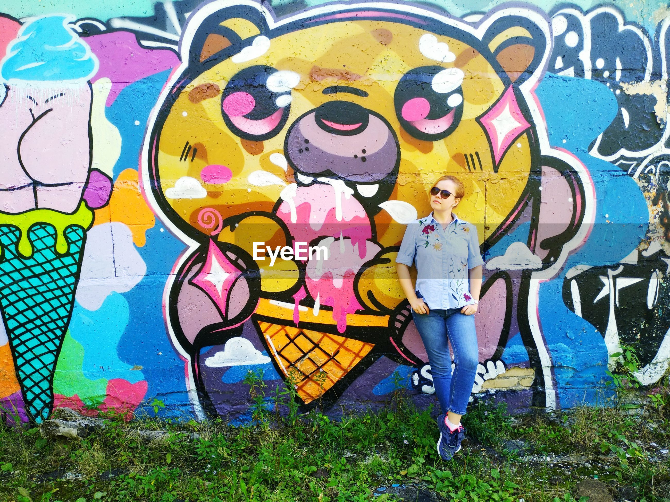 Full length of young woman wearing sunglasses standing by graffiti wall