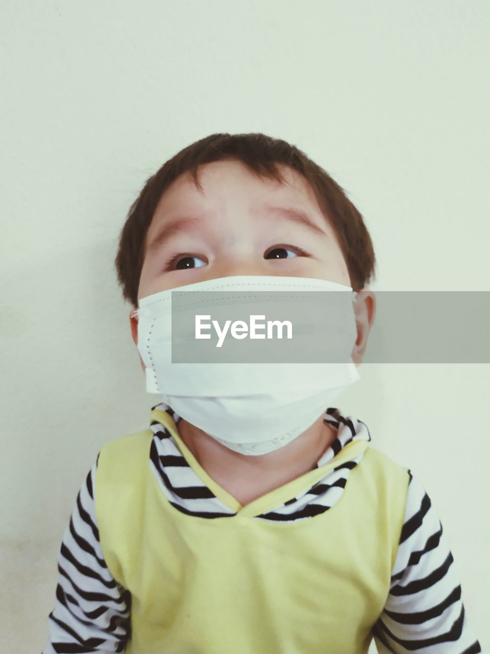 portrait, looking at camera, front view, indoors, child, one person, childhood, headshot, studio shot, casual clothing, men, boys, males, wall - building feature, surgical mask, security, white background, real people, obscured face