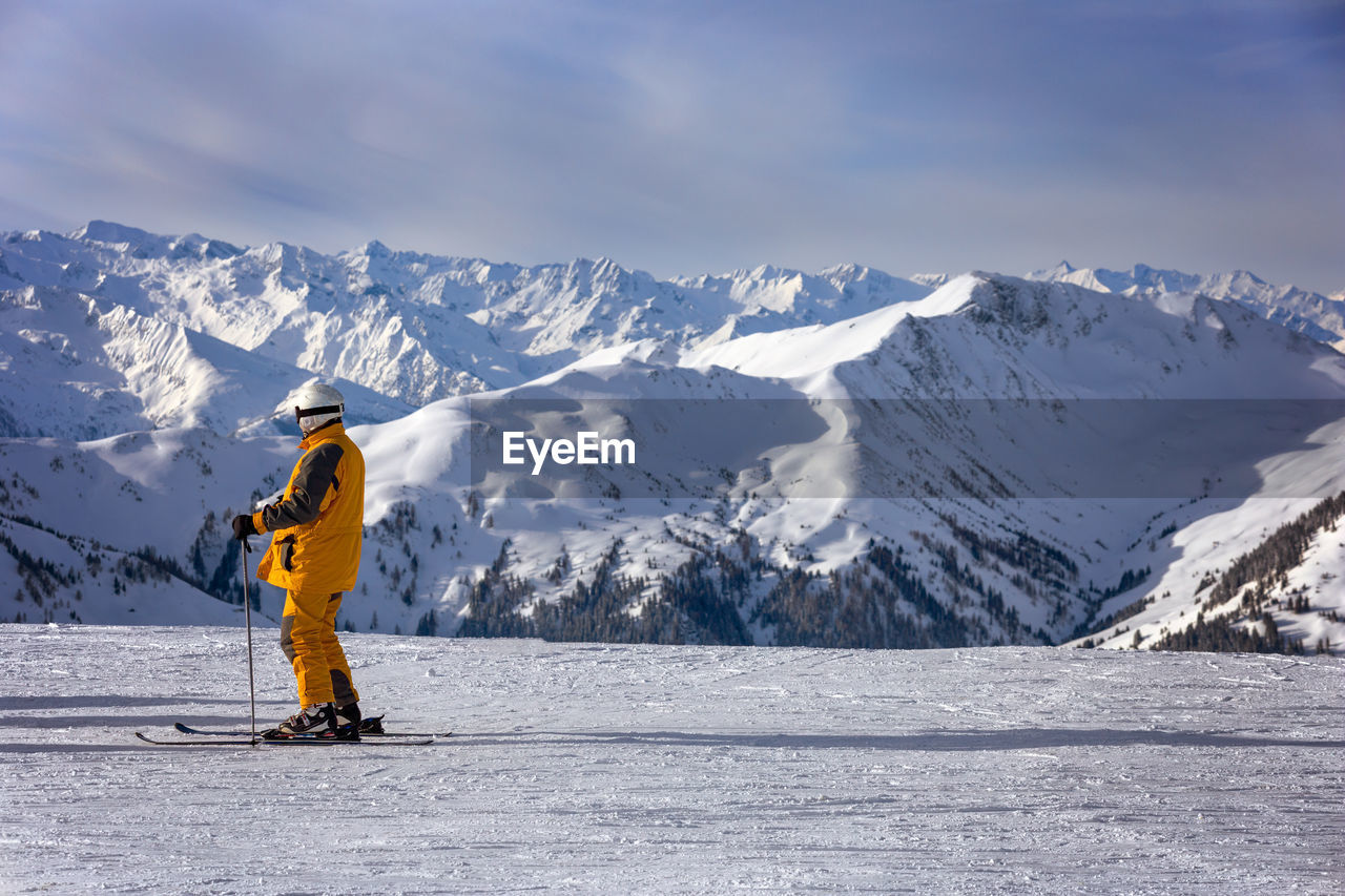 REAR VIEW OF PERSON SKIING AGAINST SNOWCAPPED MOUNTAIN