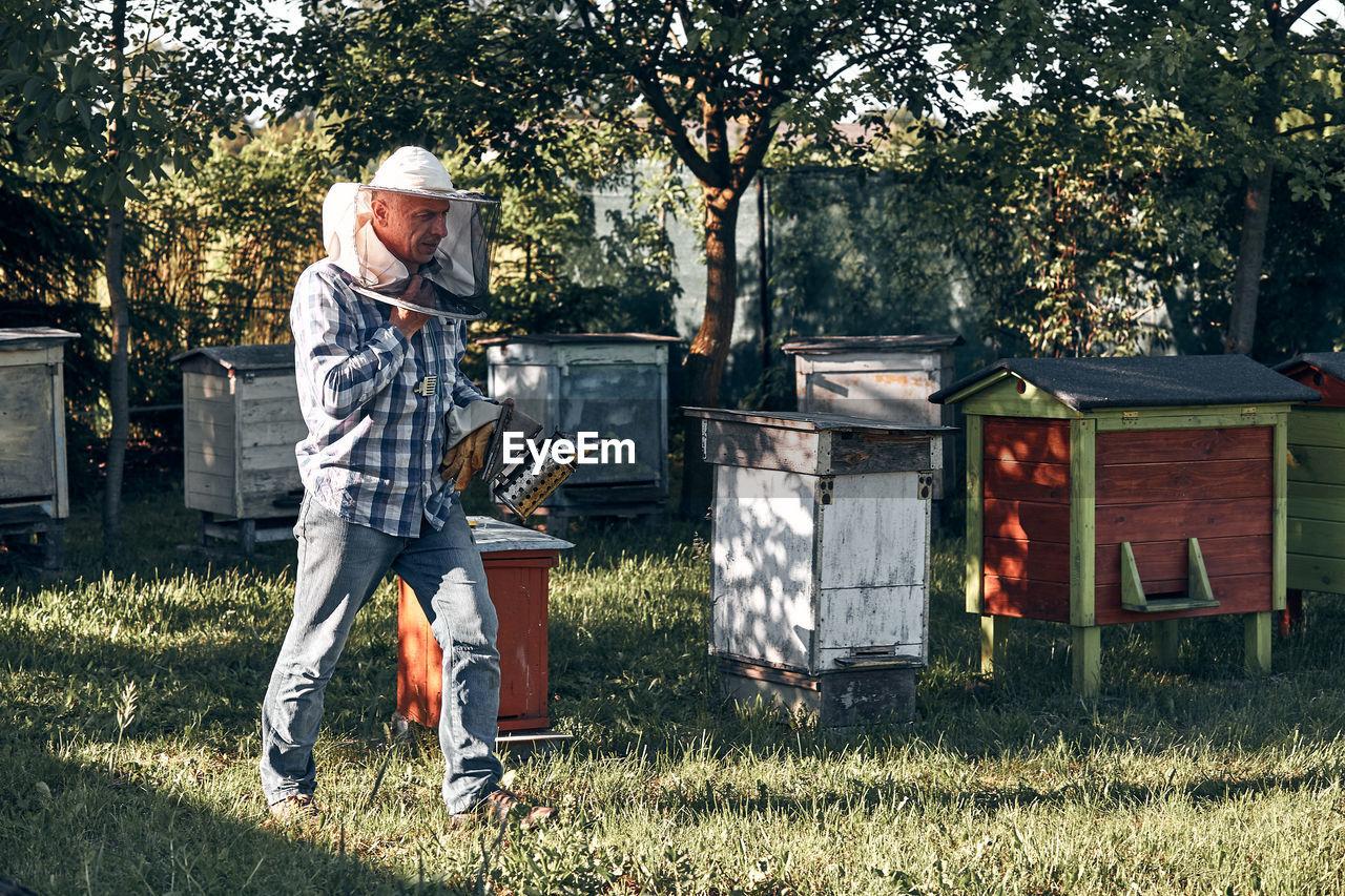 Beekeeper holding smoker while walking in yard