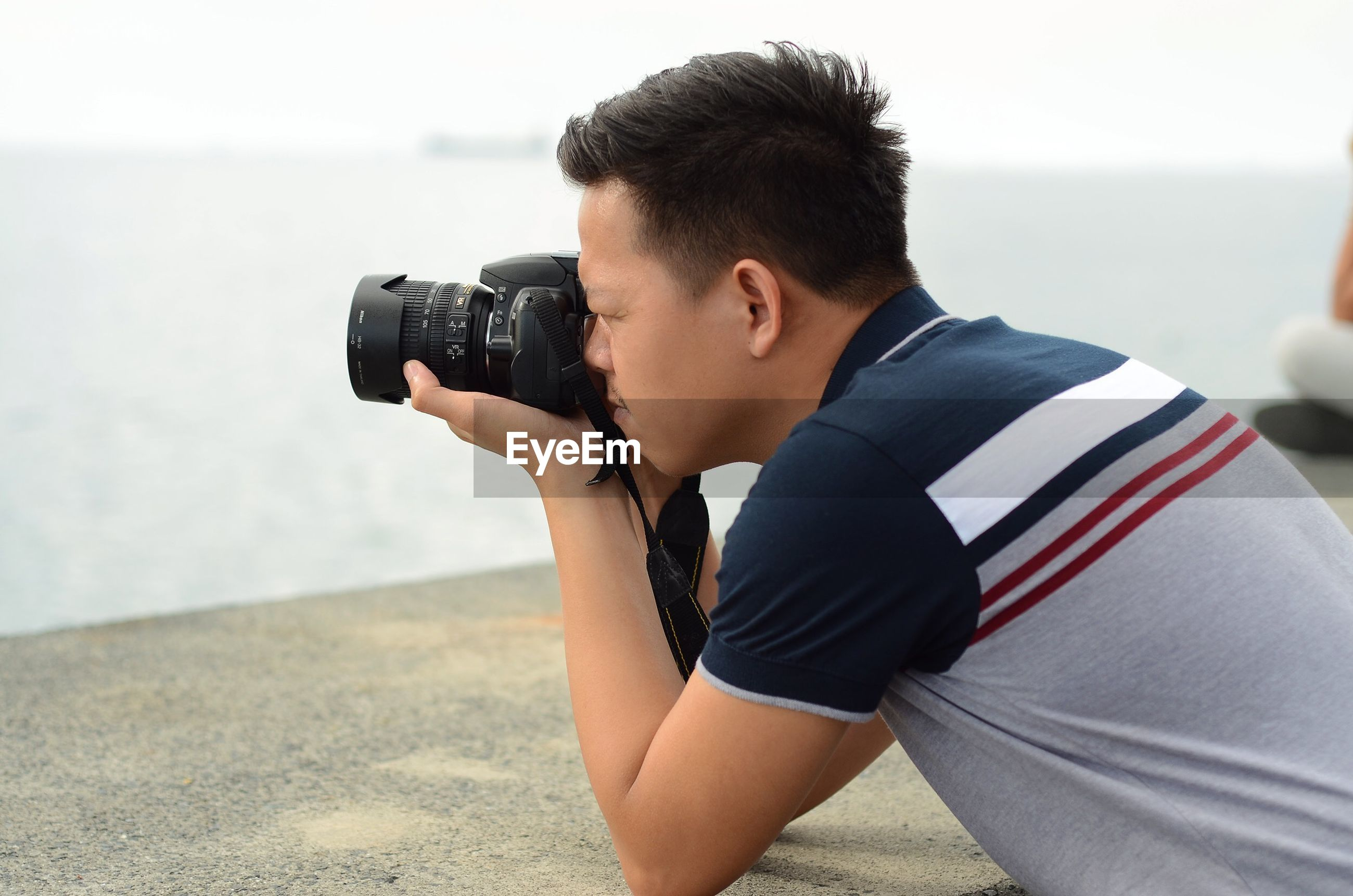 Side view of man photographing sea with camera
