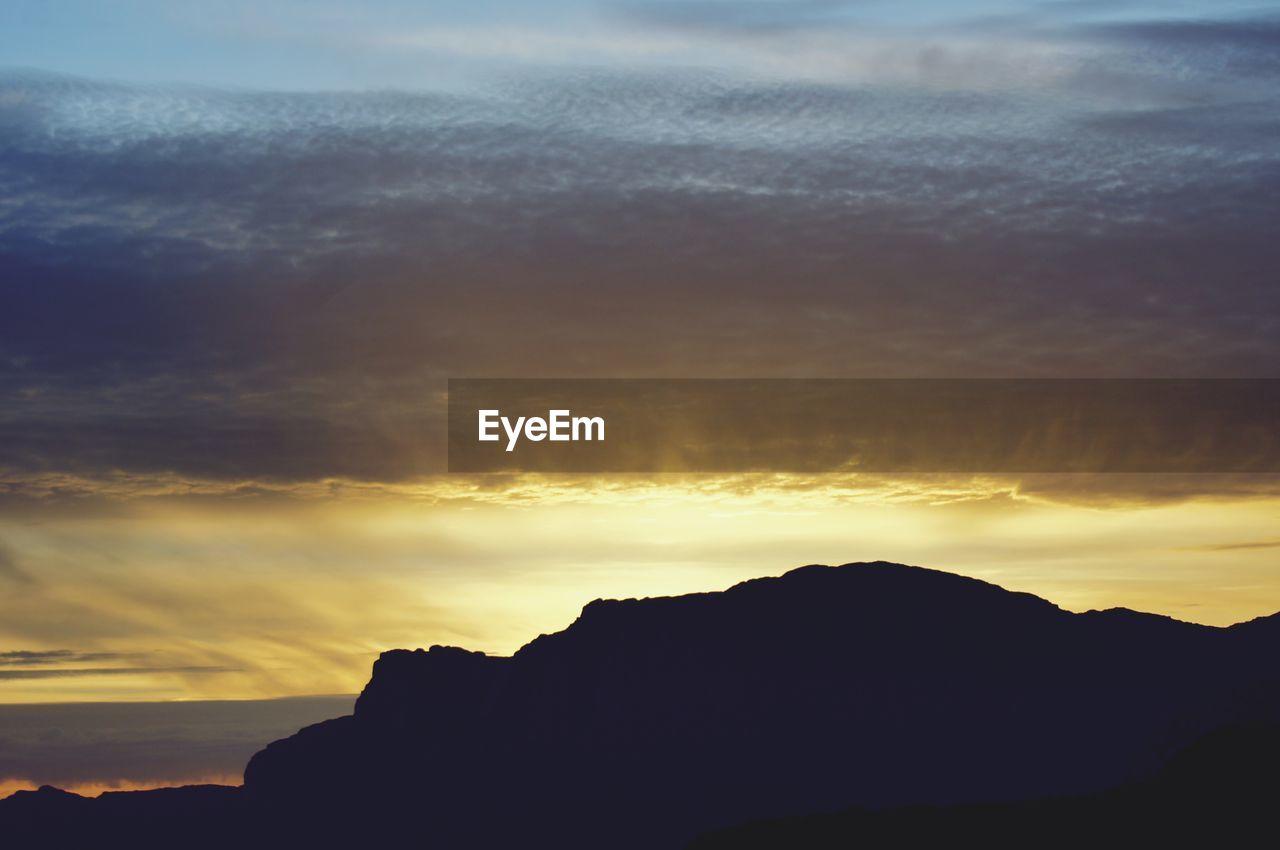 sunset, sky, silhouette, cloud - sky, beauty in nature, mountain, scenics - nature, tranquility, tranquil scene, nature, idyllic, orange color, mountain range, no people, outdoors, non-urban scene, rock, environment, majestic, dusk, mountain peak