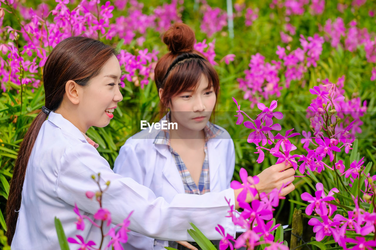 Female scientists examining pink flowers