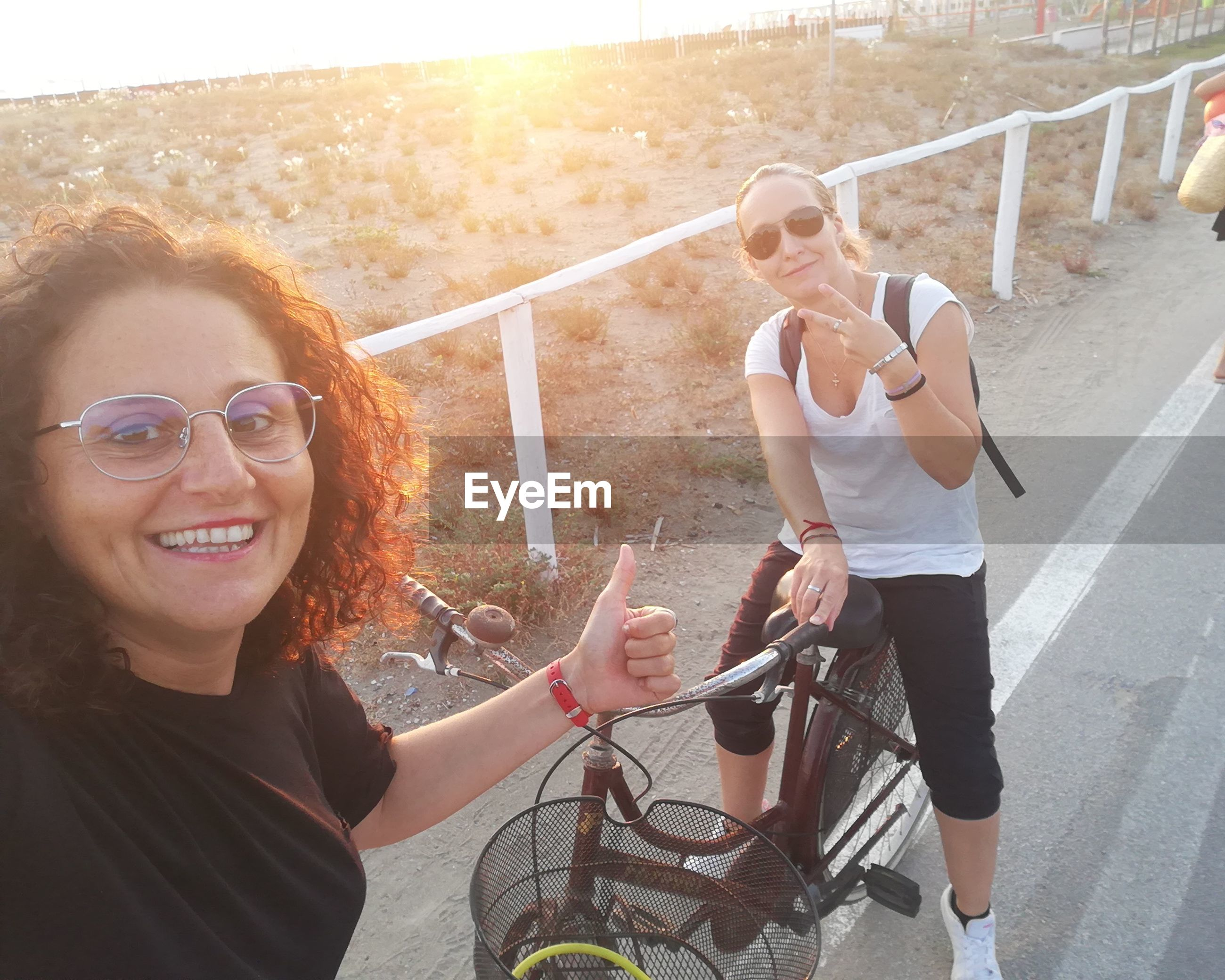 PORTRAIT OF SMILING YOUNG WOMAN RIDING SUNGLASSES ON A MAN