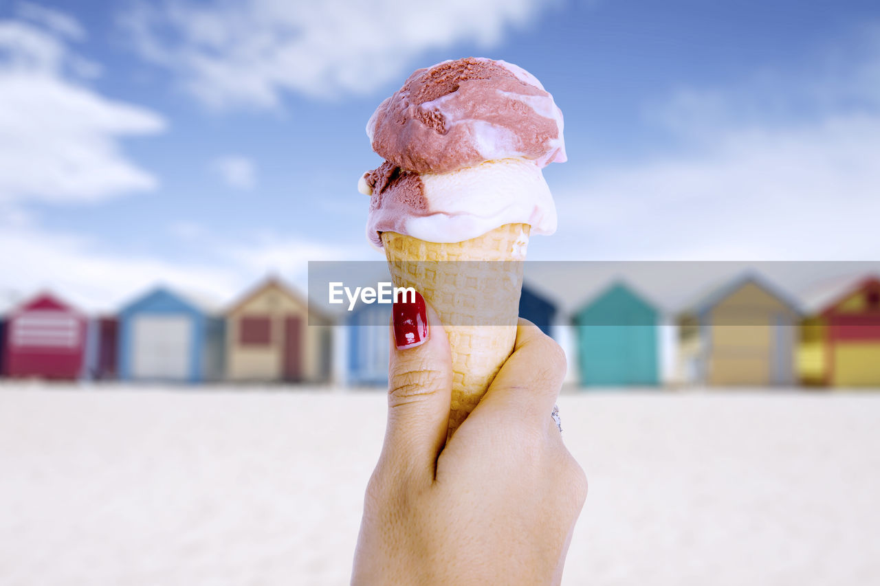 Close-Up Of Hand Holding Ice Cream Cone On Beach
