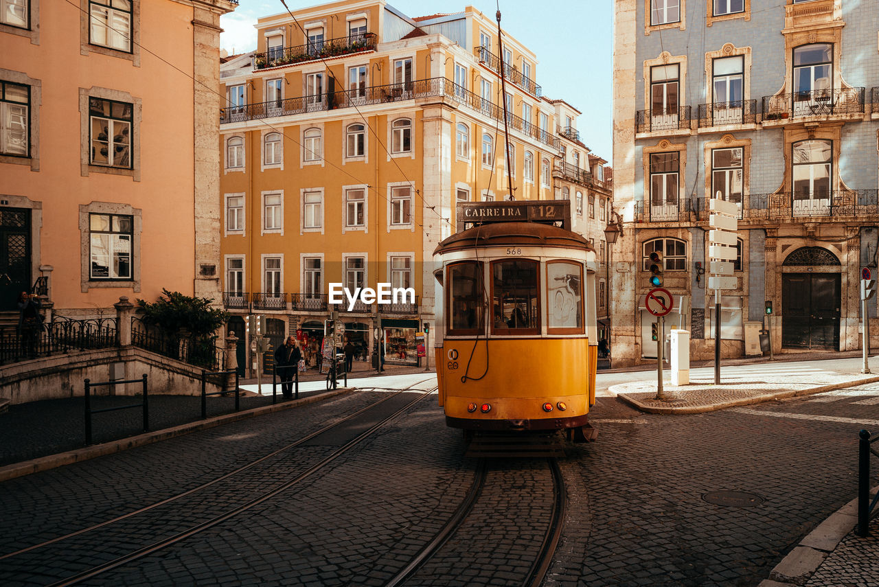 architecture, built structure, building exterior, city, mode of transportation, transportation, railroad track, cable car, track, public transportation, rail transportation, street, building, land vehicle, incidental people, day, city life, city street, outdoors, window